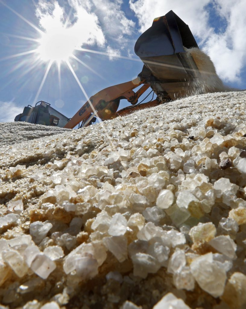 Road salt is mixed by a front-end loader before being loaded onto public works trucks Monday in Freeport.