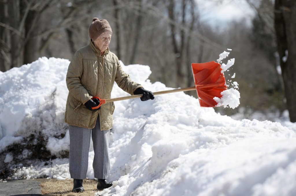 """Eighty-eight-year-old Lorraine Vassill of Saco shovels snow away from her driveway Monday. """"I'm making room for more,"""" she said during a break between throws."""