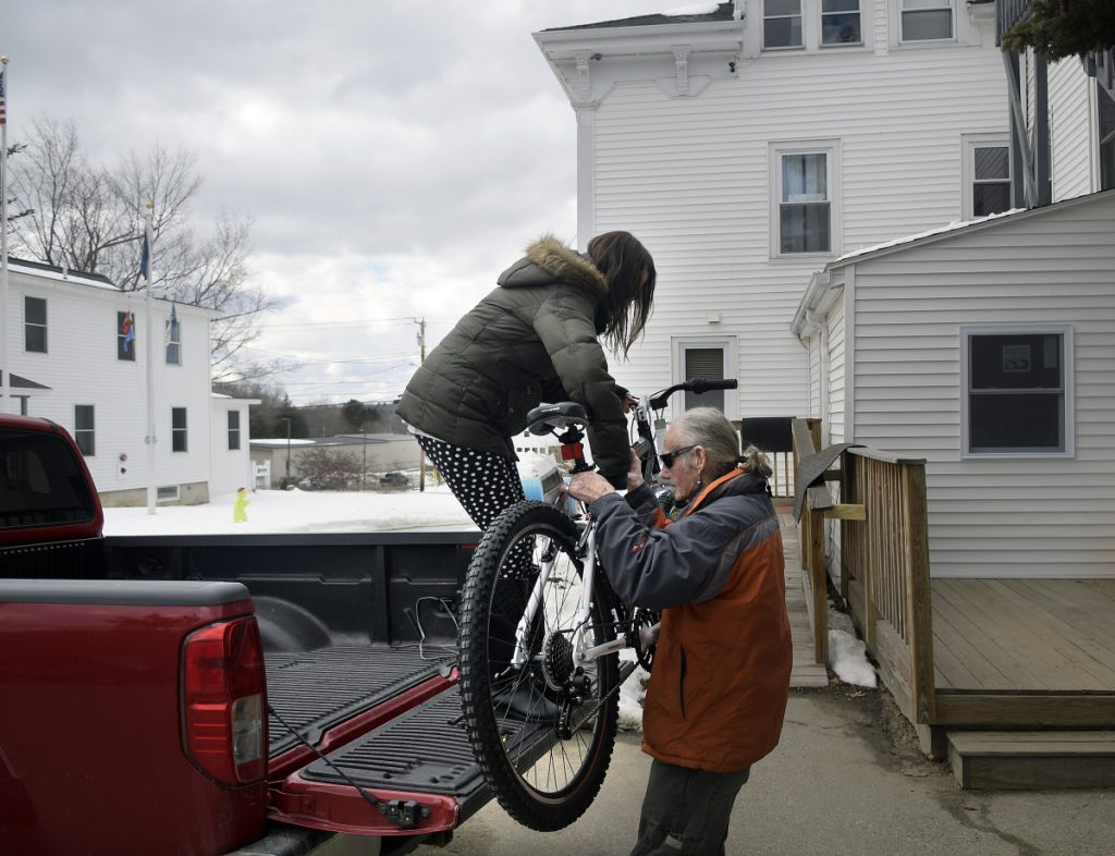 Bread of Life shelter employees Eliza Quill, left, and Gary Clark unload a bicycle they purchased for a resident of the Augusta homeless shelter on Monday.