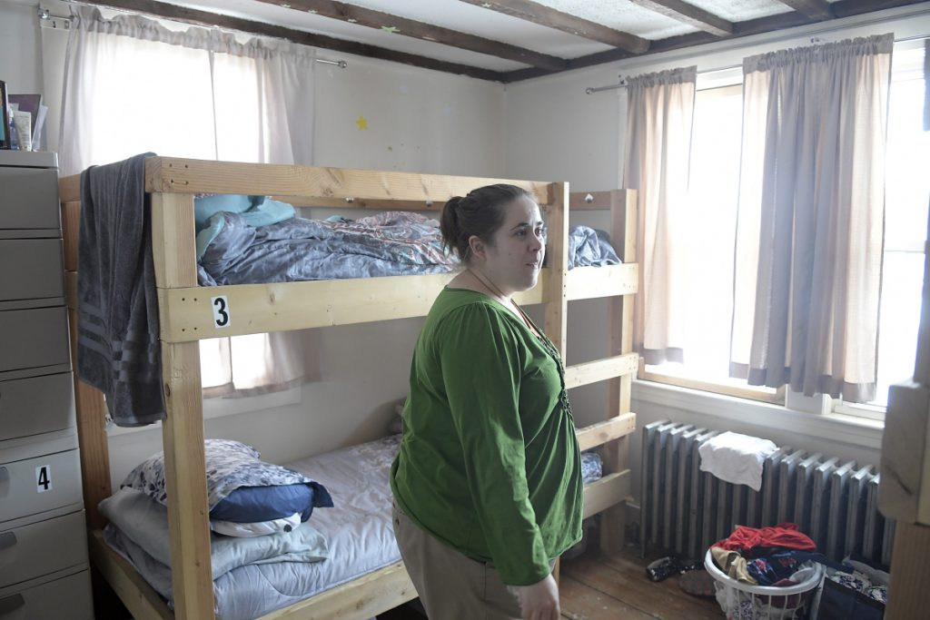 Case manager Jess Talbot walks through a bedroom at the Bread of Life Ministries shelter in Augusta on Monday. The group is planning expansions of its general homeless shelter and its shelter for veterans, which are on adjoining properties on Hospital Street.