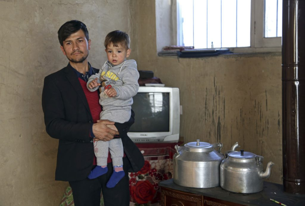 Asadullah Poya with his 18-month-old son Donald Trump, poses for a photograph at their rented house in Kabul, Afghanistan.