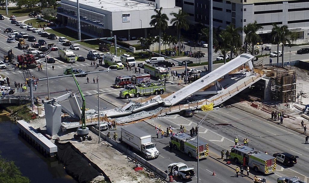 Emergency workers respond after the collapse of a new pedestrian bridge at Florida International University in Miami on Thursday. The bridge crushed multiple vehicles and killed at least four people.