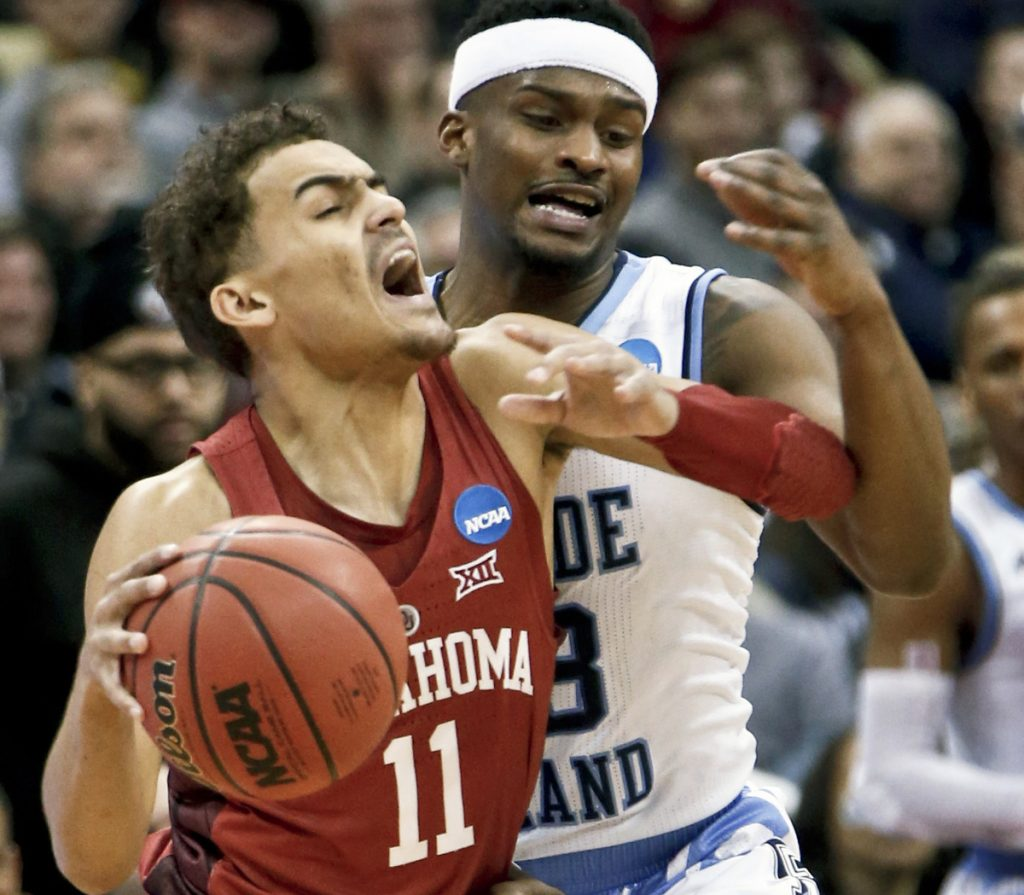 Oklahoma's Trae Young tries to get past Rhode Island defender Stanford Robinson during the first half of Thursday first-round NCAA men's college basketball tournament game in Pittsburgh. Rhode Island advanced with an 83-78 overtime win.