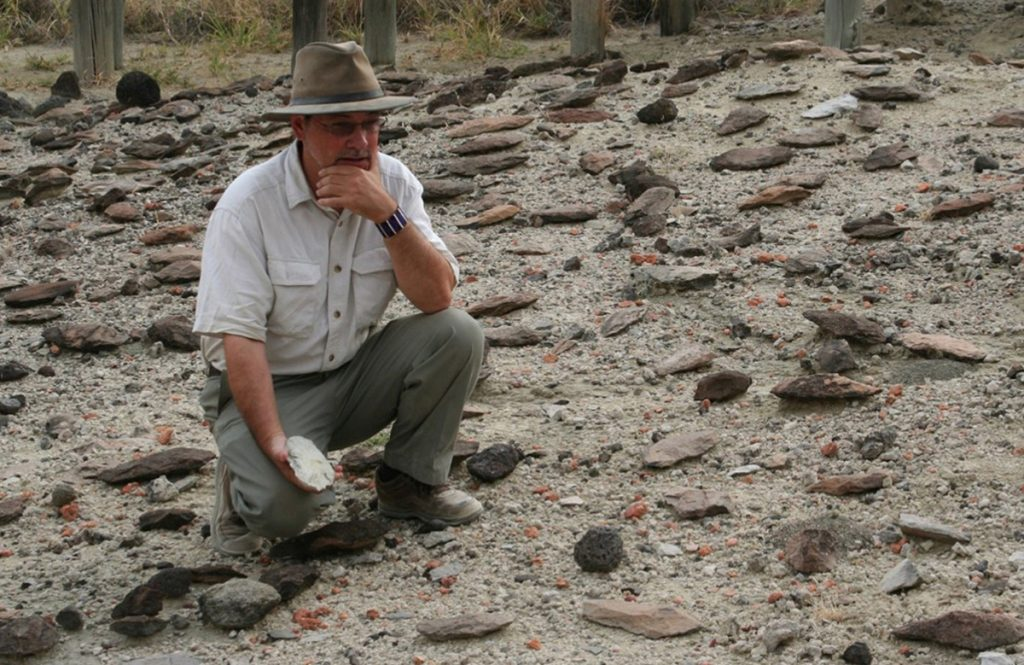 Rick Potts of the Smithsonian surveys an assortment of early stone tools in Kenya's Olorgesaile Basin.