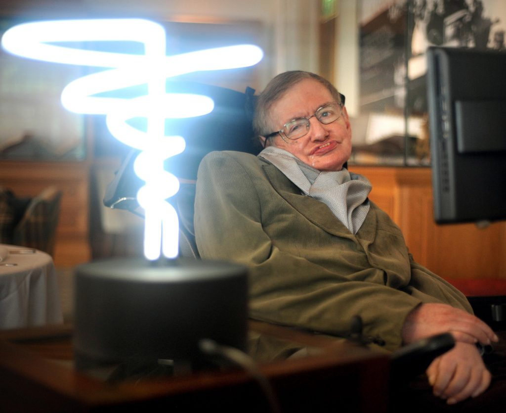 "Stephen Hawking poses in 2012 beside a lamp titled ""black hole light"" by inventor Mark Champkins, presented to him during his visit to the Science Museum in London. Hawking, whose brilliant mind ranged across time and space though his body was paralyzed by disease, died Wednesday, a University of Cambridge spokesman said. He was 76. (Anthony Devlin/PA via AP)"