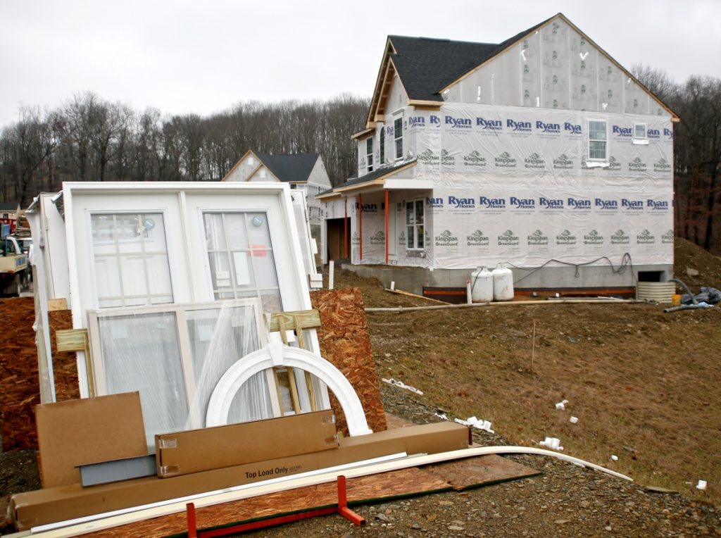 Building materials are piled near a home-construction site in Zelienople, Pa., last month. The Commerce Department on Friday reported on February's home construction data in the U.S., saying that builders have shifted focus from multifamily units to single-family houses.