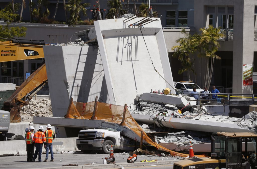 Workers stand next to a section of the collapsed pedestrian bridge Friday near Florida International University. The bridge, which was under construction, collapsed onto the busy highway Thursday, killing at least six people.