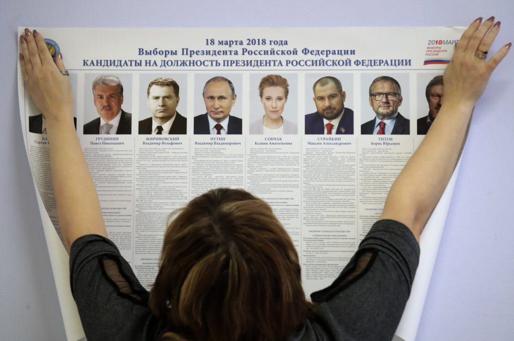 A polling station employee hangs a list of candidates for the 2018 Russian presidential election during preparations for the election at a polling station in St. Petersburg on Friday. On Sunday, presidential elections will be held in Russia. Associated Press/Dmitri Lovetsky