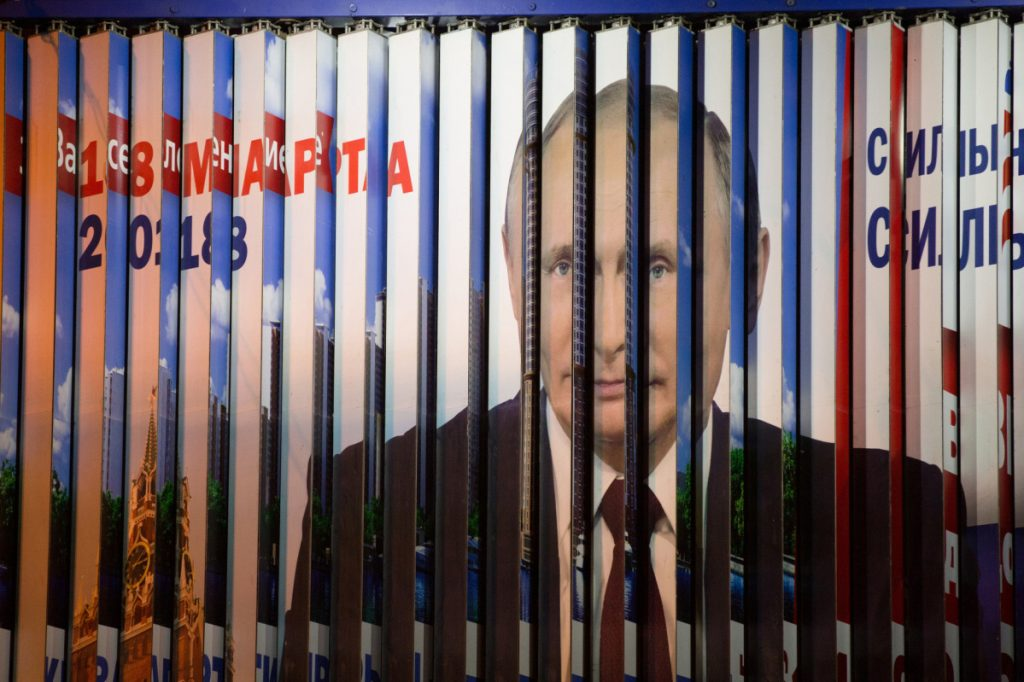 Panels rotate on an election campaign billboard poster featuring incumbent Russian President Vladimir Putin in Moscow. A monitoring group says there has been an alarming rise in complaints from employees that their bosses are pressuring them to vote.
