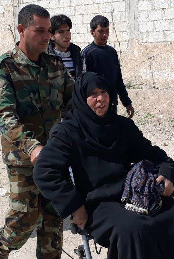 A Syrian soldier helps a woman who fled from fighting near Hamouria in eastern Ghouta on Saturday.