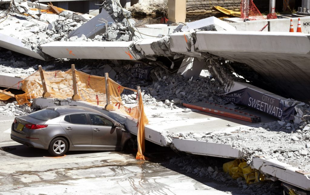 Cars are shown crushed under a section of a collapsed pedestrian bridge Friday.