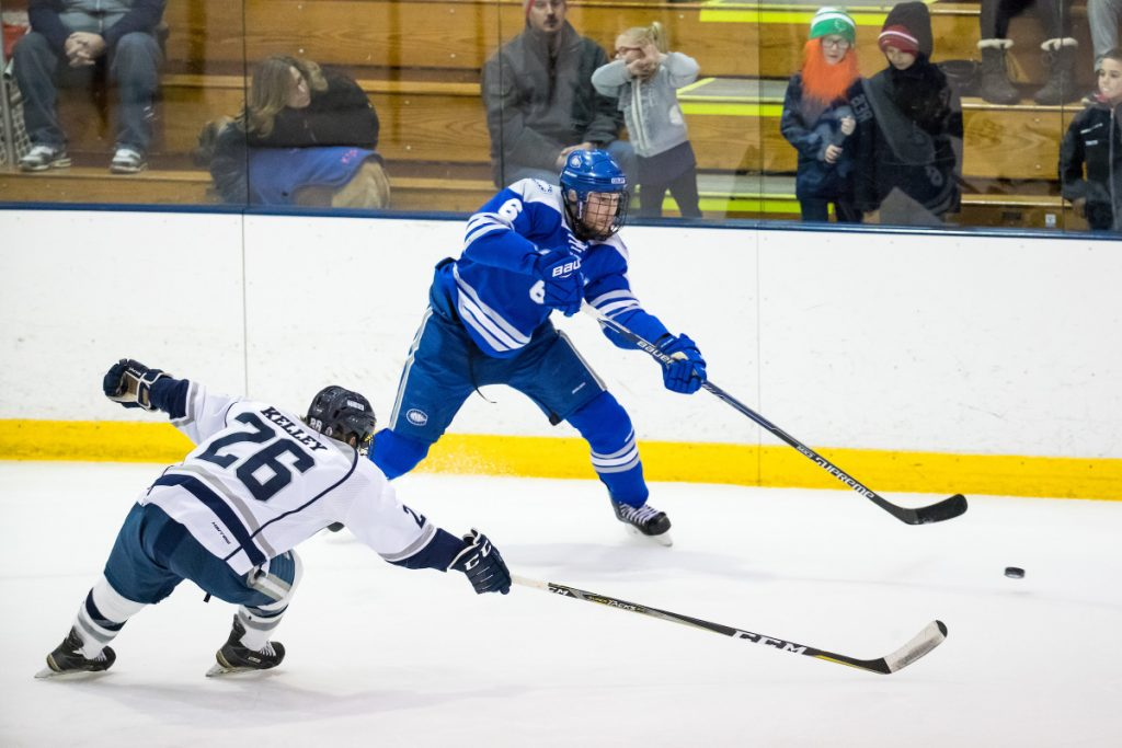 Andrew Reis of Colby makes a pass while defended by SUNY Geneseo's Carson Kelley during their NCAA Division III men's hockey quarterfinal Saturday night in Geneseo, N.Y. Colby got a goal in the closing seconds for a 2-1 win.
