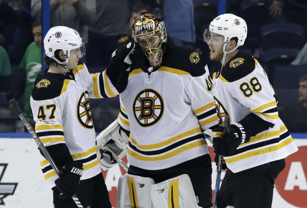 Boston Bruins defenseman Torey Krug, left, and right wing David Pastrnak celebrate with goaltender Tuukka Rask, who made 23 saves in a 3-0 win over the Tampa Bay Lightning on Saturday.