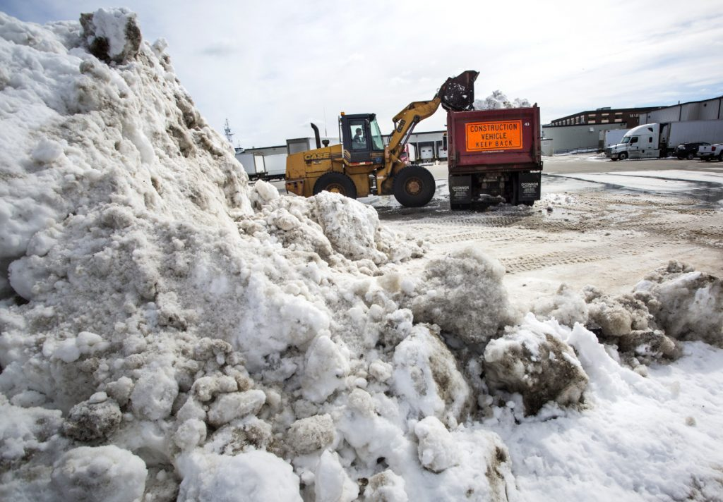 City worker Jeff Clark removes snow from a lot near Commercial Street in Portland last week. Total snowfall is 3 feet above normal this winter, and the two March nor'easters will likely push costs over the city's $1.37 million budget.