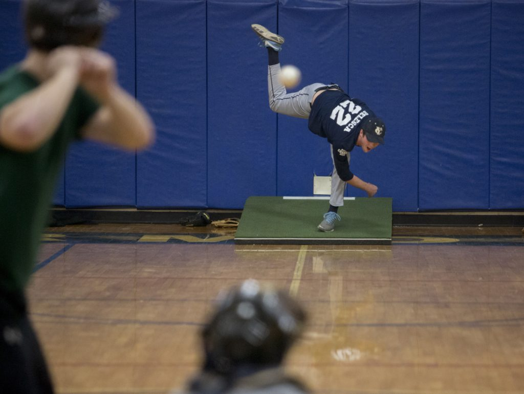 Senior Ethan Belesca, a Yarmouth High baseball pitcher, uses a makeshift mound to get in his work Monday – the first day of conditioning for pitchers and catchers around the state. Yarmouth will seek a second straight Class B state championship this season.