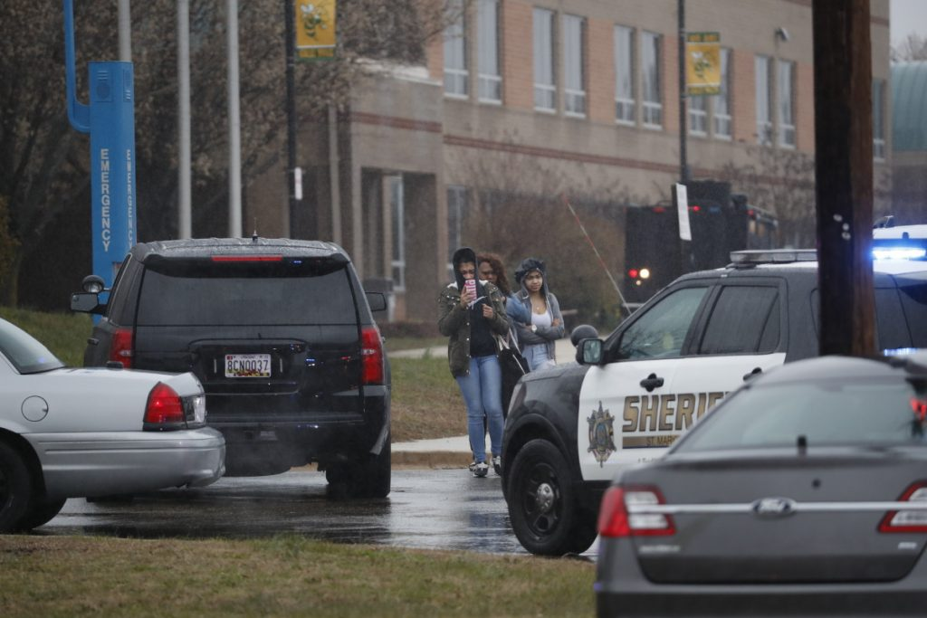 Two students and a mother leave Great Mills High School, the scene of a shooting, on Tuesday morning in Great Mills, Md.
