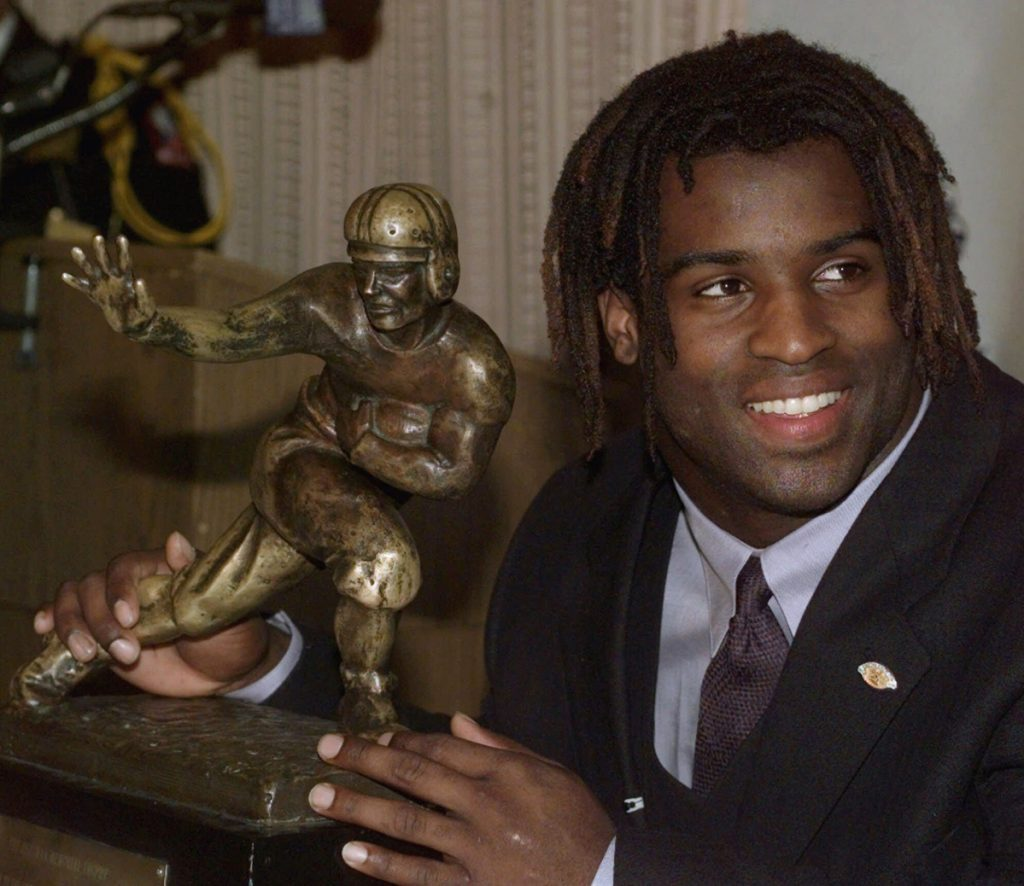 FILE - In this Dec. 12, 1998, file photo, Texas tailback Ricky Williams poses with the Heisman trophy at the Downtown Athletic Club in New York. Williams was selected Friday, Jan. 9, 2015, for for induction to the College Football Hall of Fame. (AP Photo/Suzanne Plunkett, File)