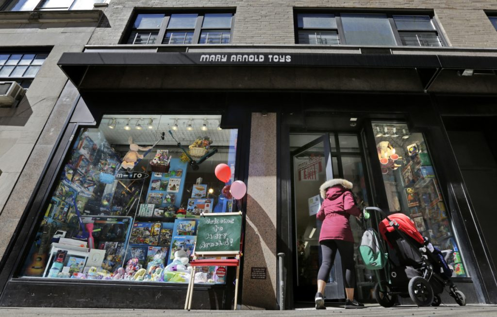 A woman pushes a stroller as she enters Mary Arnold Toys in Manhattan's Upper East Side. Many of the store's customers come in every week.