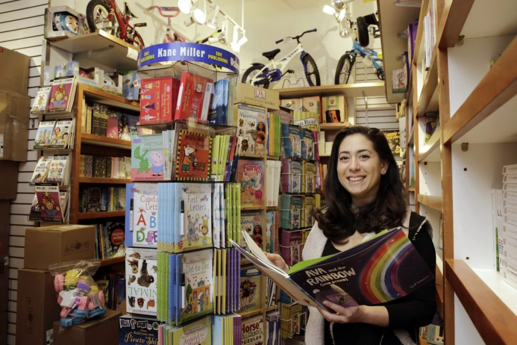 In this Monday, March 19, 2018, photo, Judy Ishayik, owner of Mary Arnold Toys, in Manhattan's Upper East Side, poses for a photo in the store's book department. Mary Arnold, a nearly 90-year-old store in Manhattan, is thriving along with many other small and independent toy stores, even as Toys R Us is going out of business and more consumers shop online. (AP Photo/Richard Drew)