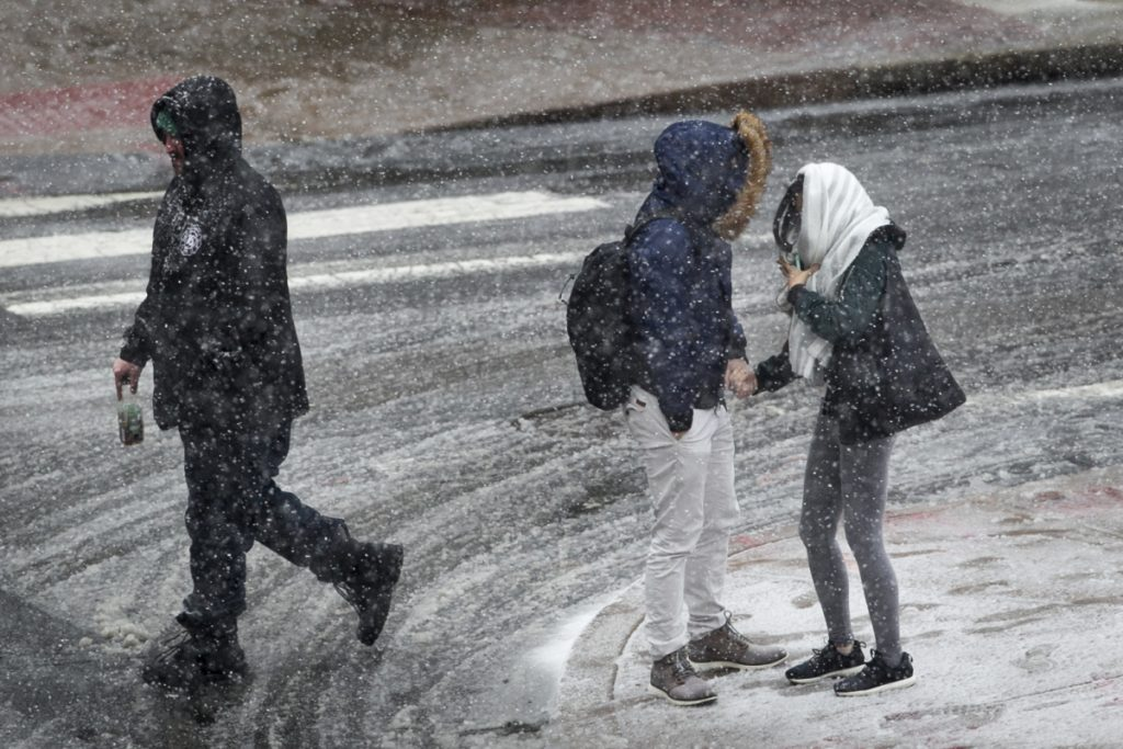 People hold hands and huddle together as snow falls in Philadelphia on Wednesday.