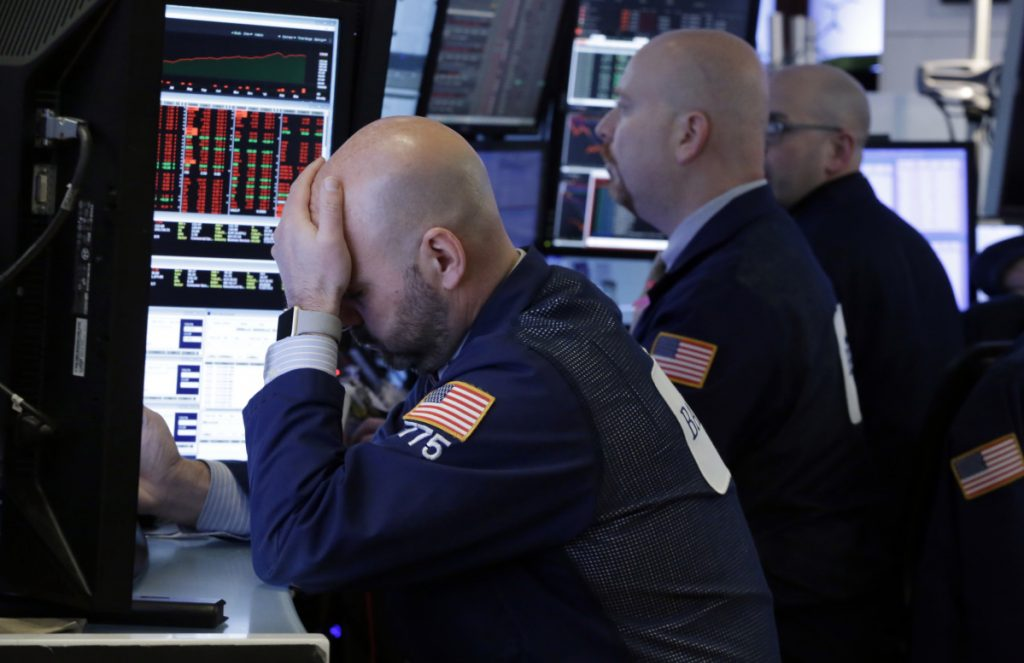 Trader Fred DeMarco, left, works with colleagues in a booth on the floor of the New York Stock Exchange on Thursday.