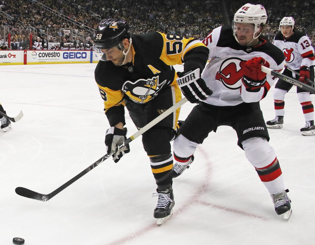 Kris Letang of the Pittsburgh Penguins skates past Sami Vatanen of the New Jersey Devils during the second period of New Jersey's 4-3 overtime victory on the road Friday night.
