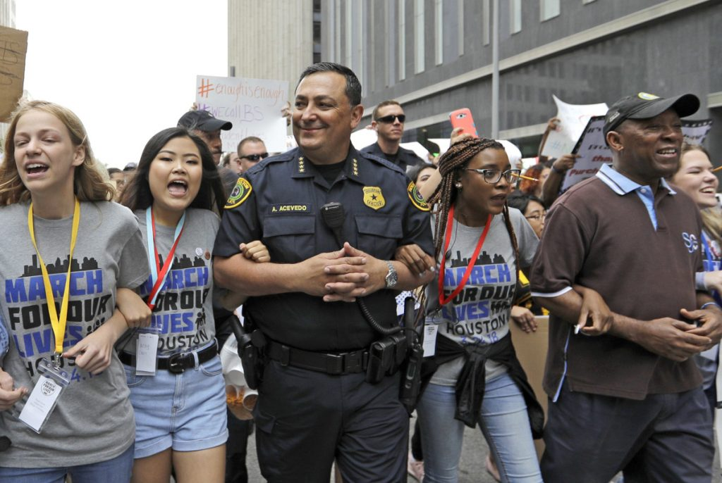 "ABOVE: Houston Police Chief Art Acevedo, center, and Mayor Sylvester Turner, far right, join demonstrators during a ""March for Our Lives"" protest for gun legislation and school safety Saturday in Houston. Turner told the crowd that adults have a responsibility to stand up and protect all children."