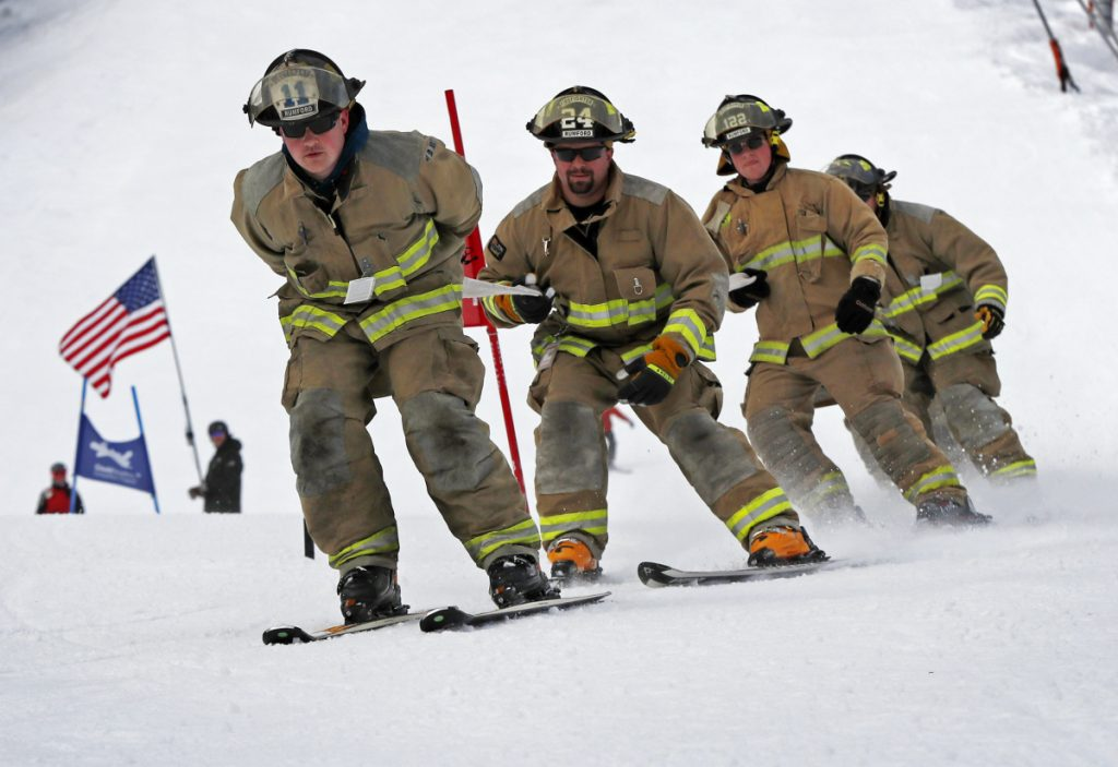 From left, Rumford firefighters Mark Arsenault, Ray Crockett and Brian Lyle and teammates compete in the 28th annual Masters of the Hose ski race at Sunday River ski resort in Newry on Sunday.