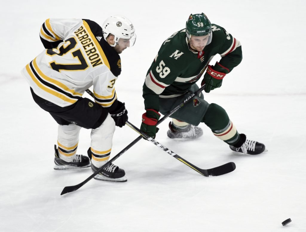Patrice Bergeron of the Bruins battles for the puck with Minnesota's Zack Mitchell during Sunday's game in St. Paul, Minn. The Bruins won in overtime, 2-1.