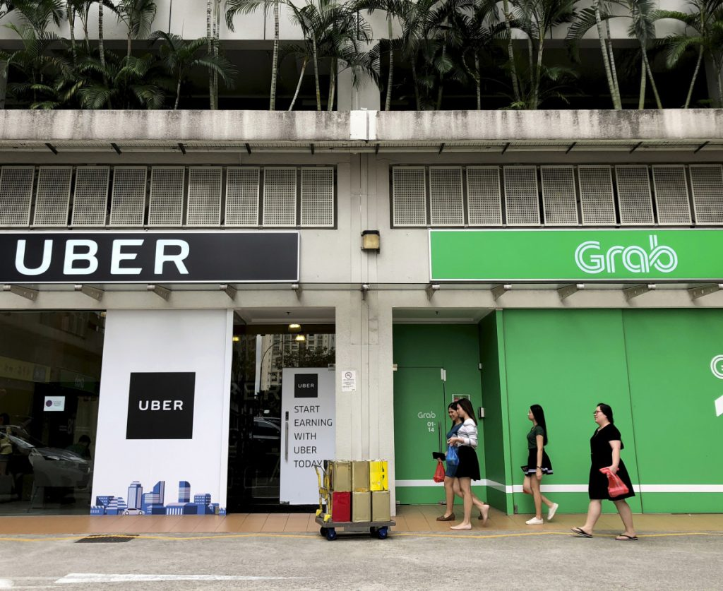 Ride-hailing rivals Grab and Uber have side-by-side offices in Singapore. As part of selling its Southeast Asia operations to Grab, Uber will get a stake in the buyer and a board seat.