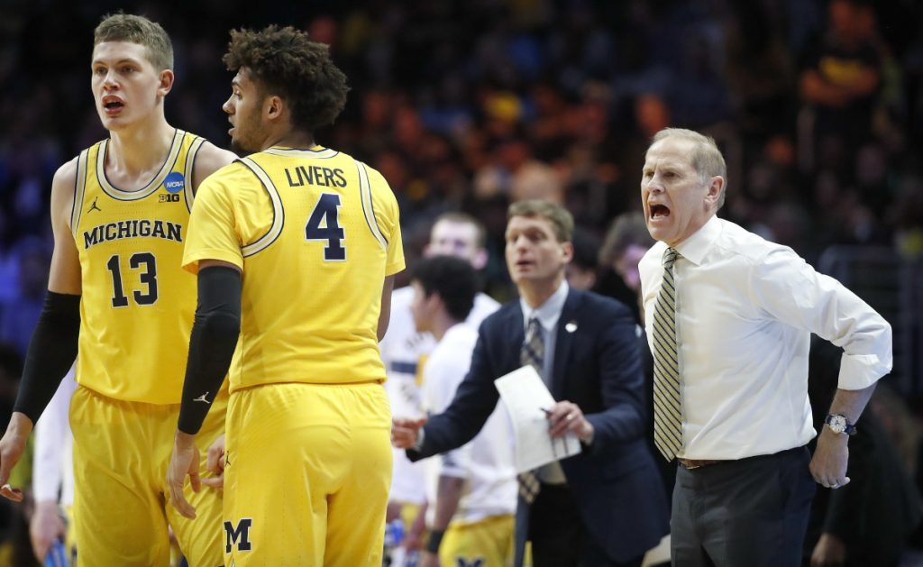 Michigan coach John Beilein, right, yells to players as forwards Moritz Wagner (13) and Isaiah Livers (4) talk during the first half of the team's NCAA men's college basketball tournament regional final against Florida State on Saturday, March 24, 2018, in Los Angeles. (AP Photo/Jae Hong)