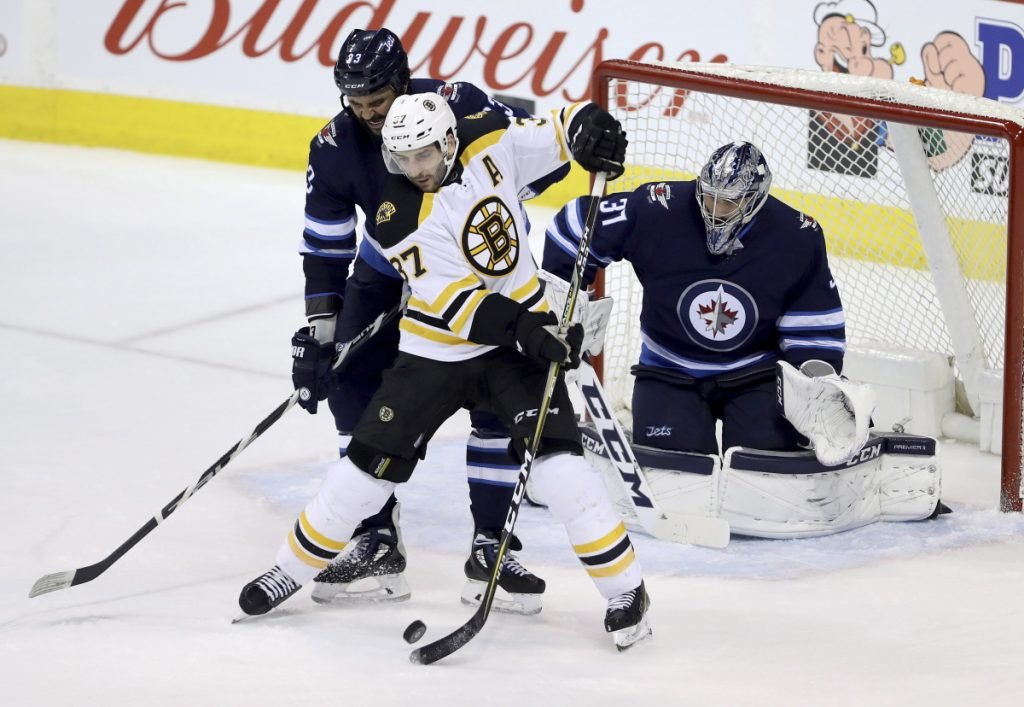 Boston's Patrice Bergeron, center, deflects a shot as Winnipeg goaltender Connor Hellebuyck, right, and Dustin Byfuglien converge during Tuesday's game in Winnipeg.