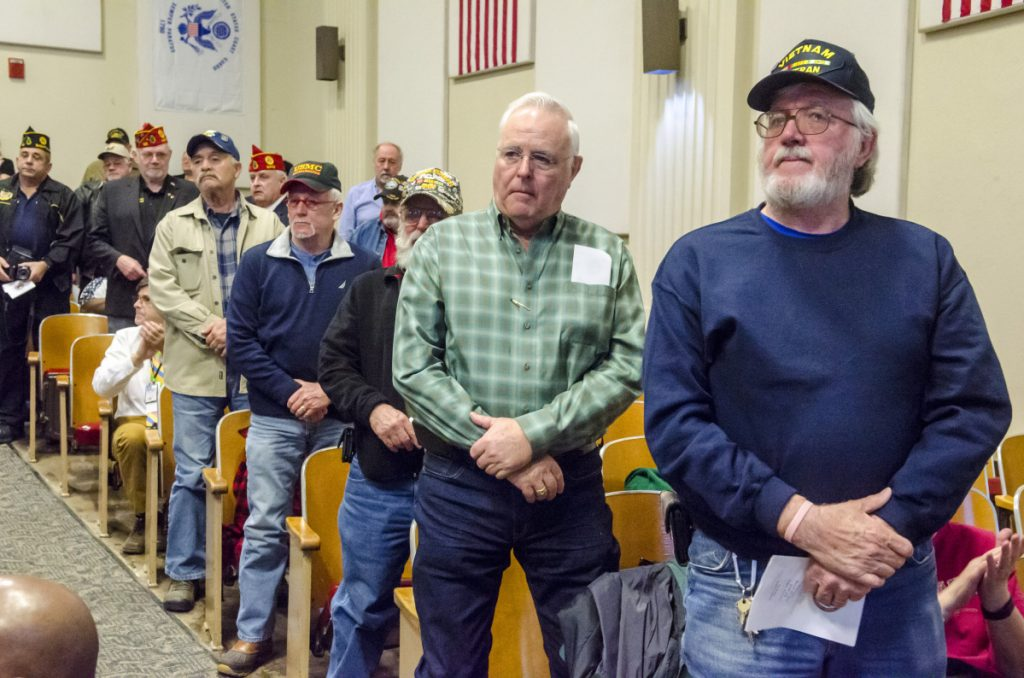 Vietnam veterans stand to be honored Thursday during a of Vietnam War 50th anniversary event at the VA Maine Healthcare Systems-Togus, which includes the federal hospital outside Augusta.