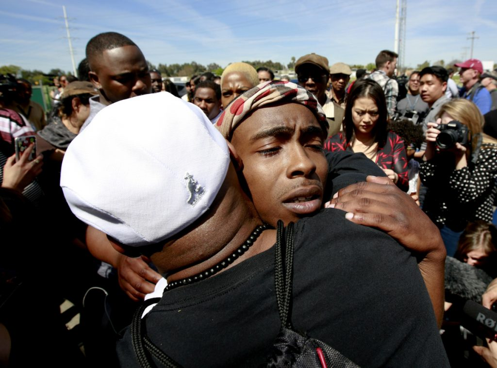Stevante Clark, the brother of police shooting victim, Stephon Clark, is consoled by a supporter after Stephon Clark's funeral on Thursday in Sacramento, Calif.