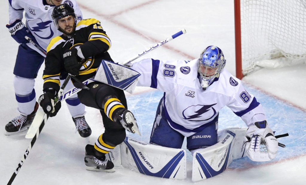 Tampa Bay Lightning goaltender Andrei Vasilevskiy (88) clears back Boston Bruins right wing Brian Gionta, left, during the first period of an NHL hockey game in Boston, Thursday, March 29, 2018. (