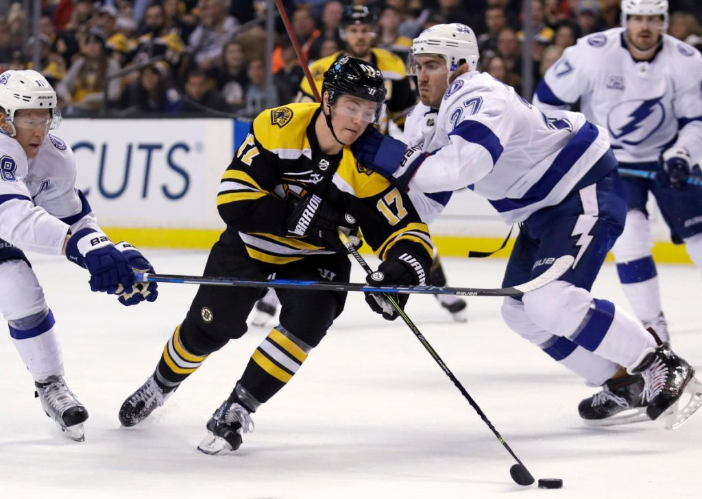 Ryan Donato of the Boston Bruins, center, is checked by defenseman Ryan McDonagh, right, and left wing Ondrej Palat of the Tampa Bay Lightning during the second period of Boston's 4-2 victory Thursday night.
