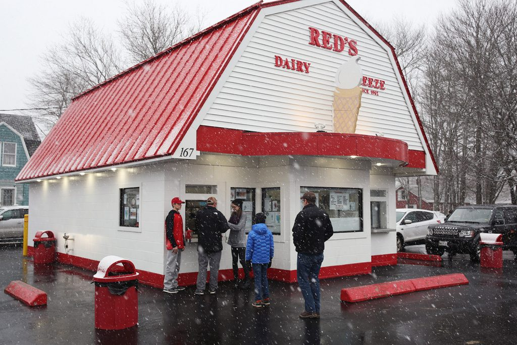 People brave an oncoming winter storm to line up outside Red's Dairy Freeze as the ice cream shop opened for the 2018 season on March 7. The 2019 season started Monday.