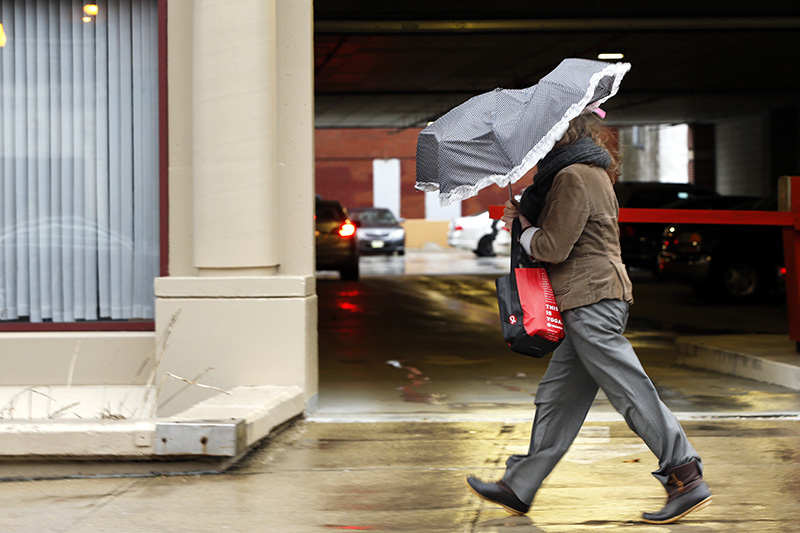 A woman walking against strong wind gusts on Middle Street takes what shelter she can under a collapsing umbrella Friday morning.