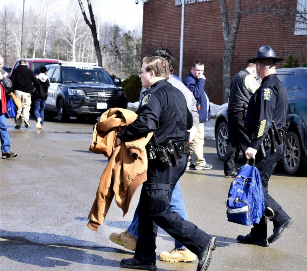 SAD 54 School Resource Officer David Daigneault, center, leads a Skowhegan Area High School student in handcuffs March 1. Another student is placed in a cruiser in the background. The action followed threats to the school that resulted in a lock-out earlier in the day.