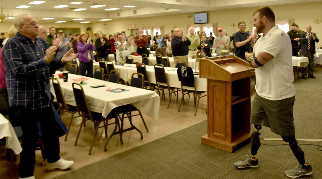 Veterans advocate Travis Mills gets a standing ovation Thursday after speaking at a National Vietnam Veterans Day celebration in Waterville.