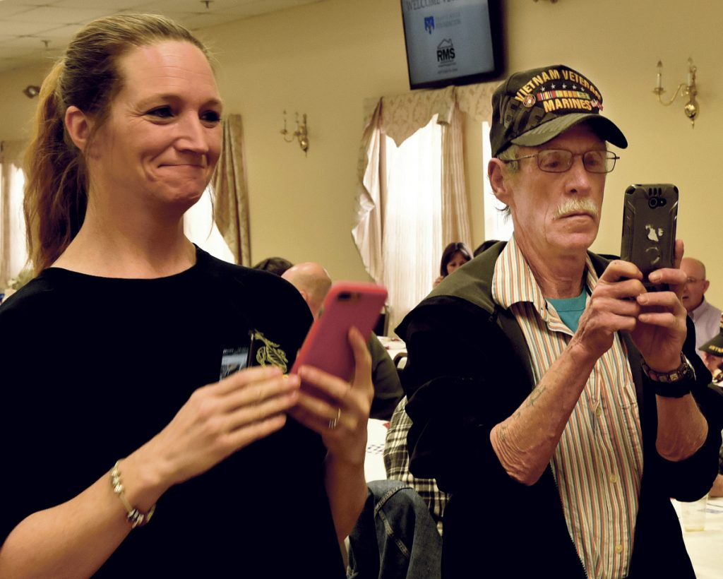 Veronica Fortier and Frank McAdoo photograph veterans advocate Travis Mills during a National Vietnam Veterans Day celebration Thursday in Waterville.