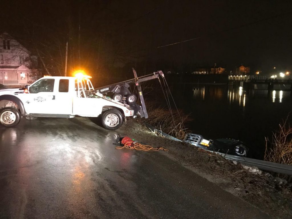 A Ford F-150 pickup truck is hauled out of the Kennebec River early Friday. A wet, cold William Sweet claimed to be a passenger in the truck, but police summoned him on charges of operating under the influence and operating without a license.