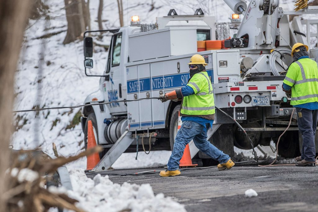 Crew members from Pike electric company from Maryland pull a downed power line on New Road in Aston, Pa., in order to reconnect it on Thursday.