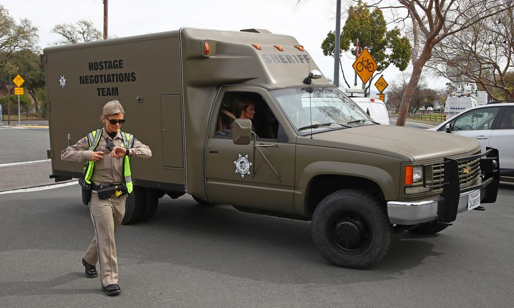 A hostage negotiation team passes a California Highway Patrol checkpoint at the Veterans Home of California on Friday after a gunman took hostages at the home. Police said Friday night that the gunman was not communicating with them.