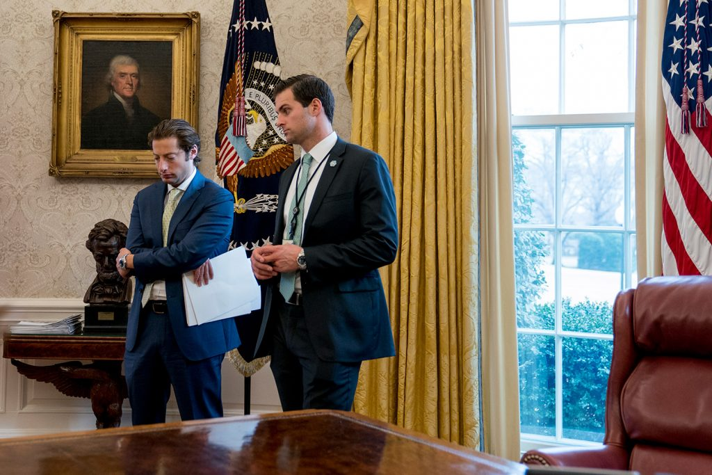 White House aide John McEntee, right, and Treasury Secretary Steve Mnuchin's Chief of Staff Eli Miller, stand in the Oval Office on Jan. 31. McEntee is leaving the White House and will rejoin Trump's campaign.