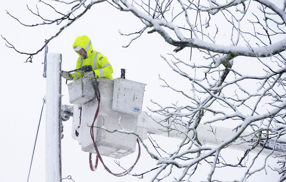 A worker repairs power lines in Norwell, Mass., during the nor'easter that socked New England on Tuesday, knocking out power to tens of thousands.