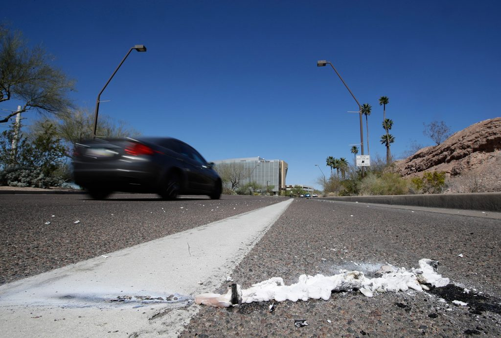 Cars pass the scene where a pedestrian was stuck by a self-driving vehicle this month in Tempe, Ariz. The vehicle was in autonomous mode with an operator behind the wheel when a woman walking outside a crosswalk was hit. Uber suspended all of its self-driving testing Monday.