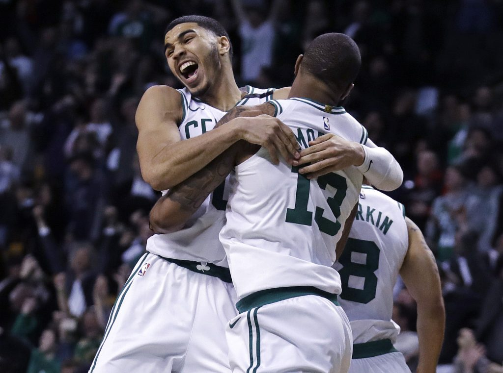 Boston's Marcus Morris leaps into the arms of Jayson Tatum as they celebrate Morris' winning 3-point shot Tuesday night in Boston.