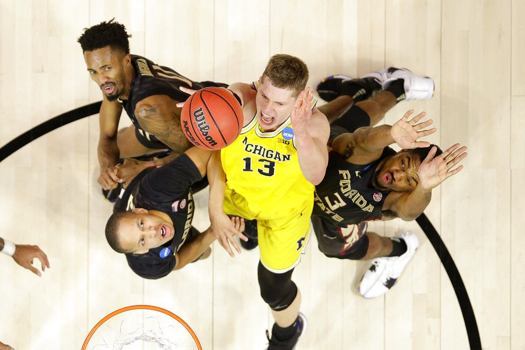 Michigan forward Moritz Wagner (13) shoots between Florida State's Braian Angola, upper left, CJ Walker, lower left, and Trent Forrest during the second half of an NCAA men's college basketball tournament regional final Saturday in Los Angeles.