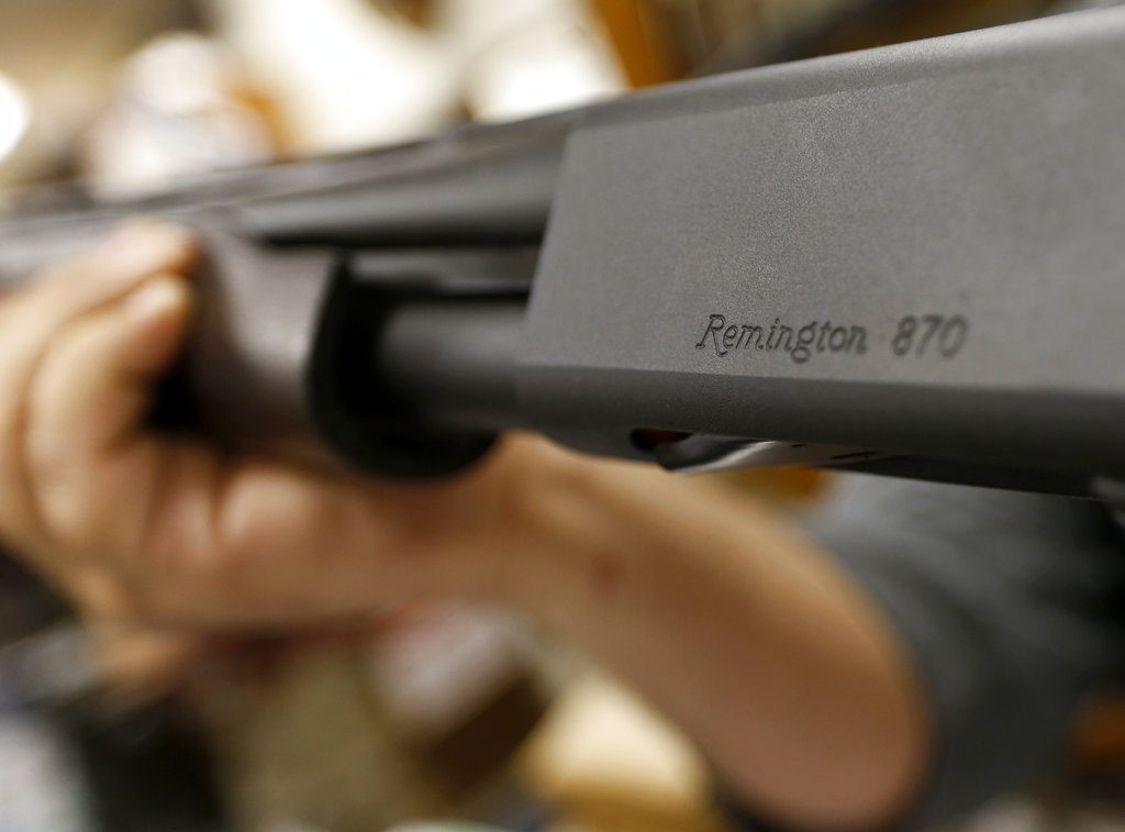 A customer hefts Remington's model 870 shotgun at Duke's Sport Shop in New Castle, Pa. The company has been making firearms since 1816.